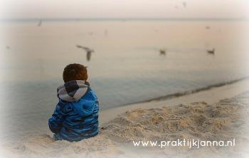 kind alleen kijkend naar de zee