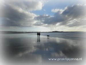 Een koppel wandelt op een leeg strand